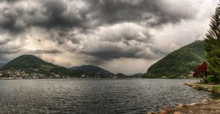 Clouds over the mountains and Lugano lake Royalty Free Stock Photography