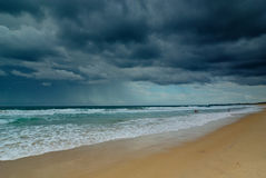Dark Clouds over Ocean. Dramatic seascape with dark clouds over the ocean and the beach Stock Image