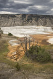 Dark clouds over an orange geothermal area, Yellowstone National Stock Photography