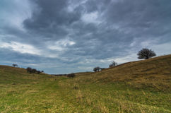 Dark clouds over the prairie path surrounded by a small hills dunes and rare vegetation Stock Images
