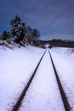 Dark clouds over a snow-covered train track in rural Carroll Cou Stock Image