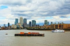 Thames River Canary Wharf view London United Kingdom. Dark clouds over Thames River and Canary Wharf tall buildings seen from the northern river bank.Photo taken royalty free stock images