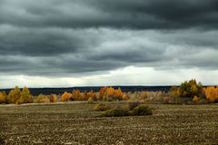 Dark clouds over the wooded area and field in autumn Stock Photo