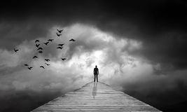 Dark clouds, path to unknown, destiny, lost, rebirth. Dark black clouds, dramatic sky, black birds flying. Lake dock path into unknown, man silhouette at the end stock illustration