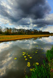 Dark clouds reflected in the canal. This was taken at a canal leading to Delft, the Netherlands. There were dark clouds that were reflected in the calm water Royalty Free Stock Photos