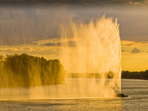 Dark clouds and strong wind create water curtain from artificial geysir against sunset light on Ada lake in Belgrade. Serbia royalty free stock photos