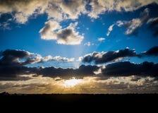 Dark clouds with sun rays over sea. Stock Photos