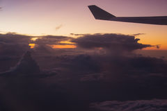 Dark clouds at sunrise during flight by airplane. Soft focus Stock Photo