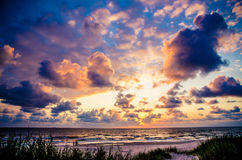 Dark clouds at sunset. Sunset behind dark Clouds over Sea Royalty Free Stock Photos