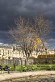Dark clouds, thunderstorm, park in Paris center. City stock photo