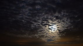 Dark clouds are transforming and moving across the night sky and moon. Time-lapse. UHD - 4K stock footage