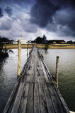 Dark clouds at wooden jetty. sandy beach on the horizon and mosque Royalty Free Stock Photo