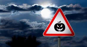 Full Moon in the Night Sky and Halloween Road Sign. Dark Cloudy Sky with Full Moon and the road Sign white Triangle with a Red Border `Caution, Halloween` is a Royalty Free Stock Images