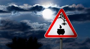 Full Moon in the Night Sky and Witch Road Sign. Dark Cloudy Sky with Full Moon and the road Sign white Triangle with a Red Border `Caution, Halloween` is a black Stock Photography