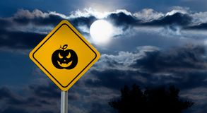 Full Moon in the Night Sky and Halloween Road Sign - Pumpkin. Dark Cloudy Sky with Full Moon and the road Sign Yellow Square `Caution, Halloween` is a black Royalty Free Stock Image