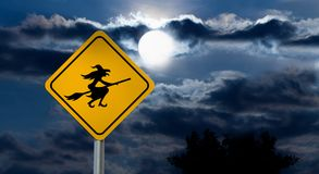 Full Moon in the Night Sky and Witch Road Sign. Dark Cloudy Sky with Full Moon and the road Sign Yellow Square `Caution, Halloween` is a black Silhouette of the Stock Photos