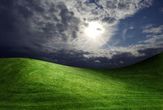 Dark cloudy sky and green grass royalty free stock photography