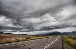 Dark, cloudy sky over road Royalty Free Stock Image