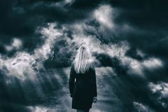 Dark cloudy sky with woman walking Stock Images
