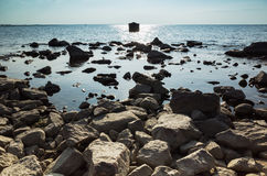 Dark coastal stones and shining sea water Stock Photo