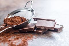 Dark cocoa powder in a sieve and chocolate. Dark cocoa powder in a sieve and chocolate on old kitchen table Royalty Free Stock Photography