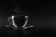 Dark coffee beans on glass cup Stock Photos