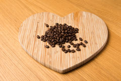 Dark Coffee Beans on Heart Shaped Chopping Board. On a wooden table Stock Images