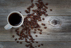 Dark Coffee and beans on rustic wood with slight vignette border Stock Photography