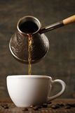 Dark coffee pours from a copper cezve into a white cup Stock Images