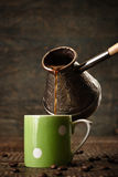 Dark coffee pours from a copper jezve into a green ceramic vinta Royalty Free Stock Image