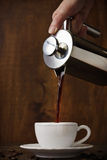 Dark coffee pours from a copper jezve into a white cup Royalty Free Stock Photo