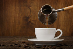 Dark coffee pours from a copper jezve into a white cup Royalty Free Stock Photography