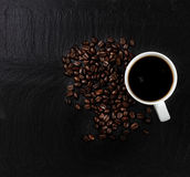 Dark coffee with roasted beans on natural slate stone background Royalty Free Stock Images