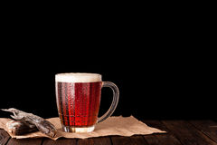 Dark cold beer in a frosty mug on dark wooden table. Dry fish on paper Stock Photography
