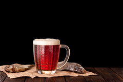 Dark cold beer in a frosty mug on dark wooden table. Dry fish on paper Royalty Free Stock Image