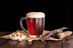Dark cold beer in a frosty mug on dark wooden table. Dry fish, pistachios on paper Royalty Free Stock Photography