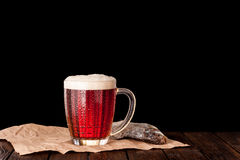 Dark cold beer in a frosty mug on dark wooden table Stock Photography