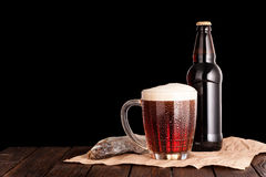 Dark cold beer in frosty mug, dry fish, brown bottle on dark woo. Dark cold beer in a frosty mug on dark wooden table. stockfish and brown bottle on paper Royalty Free Stock Photo
