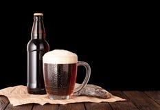 Dark cold beer in a frosty mug, stockfish, brown bottle on dark Stock Photo