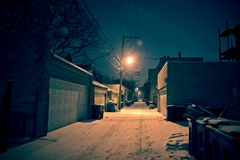 Dark cold Chicago winter alley with snow and ice at night. Dark, cold Chicago winter alley with snow and ice at night royalty free stock photo