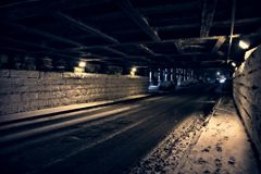 Dark and cold city train bridge tunnel underpass at night. Stock Photos