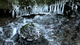 Dark cold water of mountain stream in winter time stock video