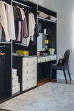 Dark color scheme modern walk in closet design with black chair. At home royalty free stock image