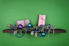 On a dark-colored shelf fixed on a green wall, coniferous branches are decorated with New Year`s toys and two boxes of gifts are royalty free stock image