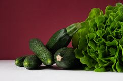 Dark colorful green vegetables on white table and bordo wall. Summer fashion food background. Dark colorful green vegetables on white table and bordo wall Royalty Free Stock Images