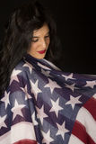 Dark complected female model wrapped in an American flag scarf. Looking down at it with respect Stock Photography