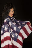 Dark complected woman with American flag draped over shoulder. Dark complected woman American flag shoulder drape royalty free stock photo