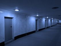 Dark concrete corridor with a closed doors. Closed doors on a side of long corridor. May be used as time and choice concept stock images