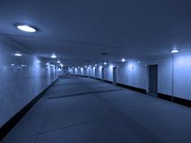 Dark concrete corridor with a closed doors. Closed doors on a side of long corridor. May be used as time and choice concept royalty free stock photos
