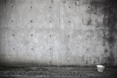 Dark concrete wall with paint bucket Stock Images